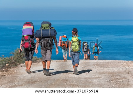 A group of tourists with large backpacks are on the sandy road to the sea - stock photo