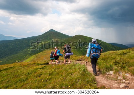 A group of tourists with large backpacks are on thunderstorm to the mountain