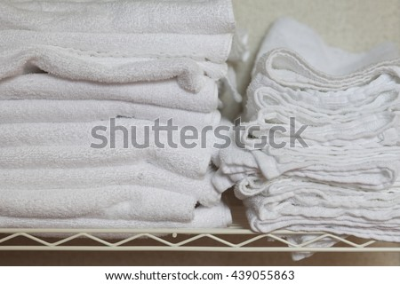 a group of towels on the shelf in hotel