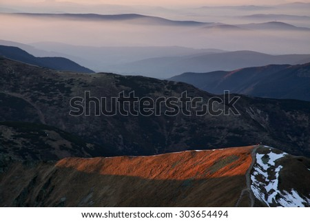 A group of trekkers on a summit with a light of an evening Sun on a ridge in Tatry Mountains, Poland - stock photo