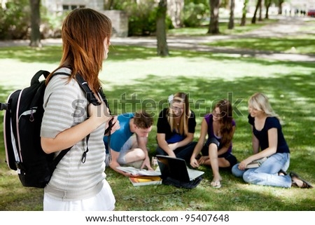A group of university students stuying together with one student in foreground - stock photo