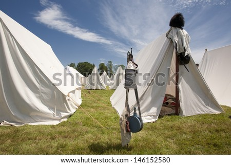 A group of white canvas tents used for the War of 1812 and Revolutionary War Reenactments. - stock photo
