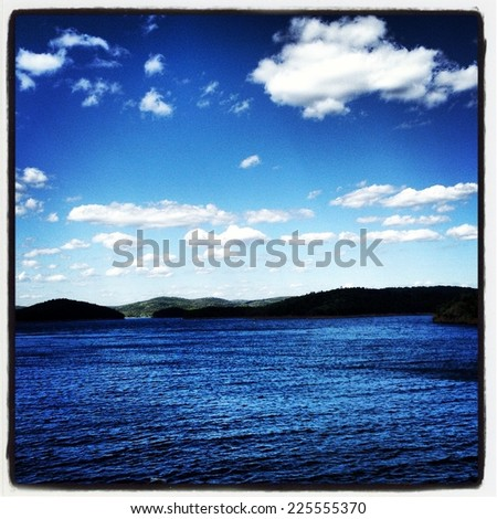 A group of white clouds among a blue sky over calm water. - stock photo