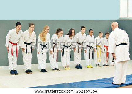 a group of young, beautiful and successful karate children, women and men posing with karate master - stock photo