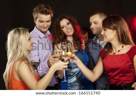 A group of young beautiful people dancing at a disco with glass of champagne - stock photo