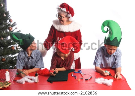 A group of young children aged 6 - 12 wearing elf hats and working with Mrs. Santa Claus on a Christmas craft project of decorating a stocking. One boy looking up at Mrs Claus