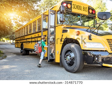A group of young children getting on the schoolbus - stock photo