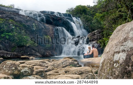 A group of young foreigners are watching the waterfall at the end of Bakers Falls in Horton plains, Sri Lanka - stock photo