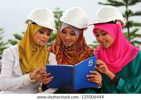 A group of young muslim architect girl with protective helmet looking something on their notebook - stock photo