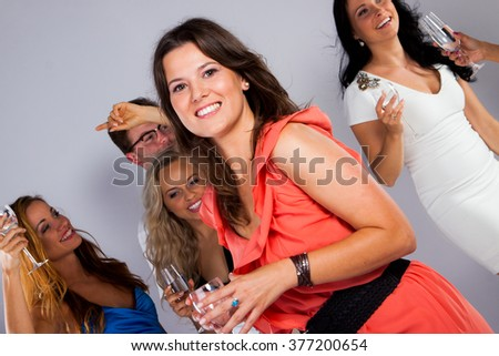 A group of young people dancing at night club. Pretty girl - stock photo