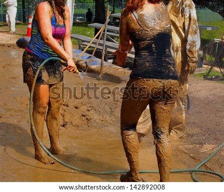 A group of young people hose mud of their bodies with cold water on a hot day in the sunshine. - stock photo