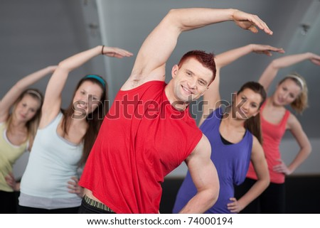 A group of young people stretching at a health club - stock photo