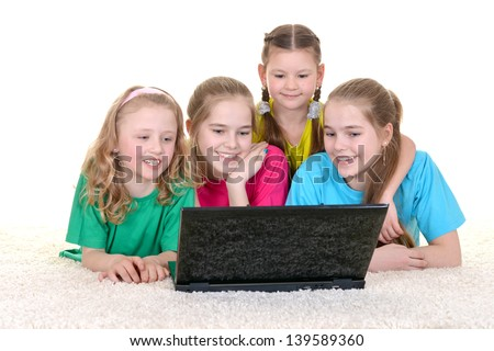 A group of young school girls in colorful T-shirts lying on the floor using laptop - stock photo