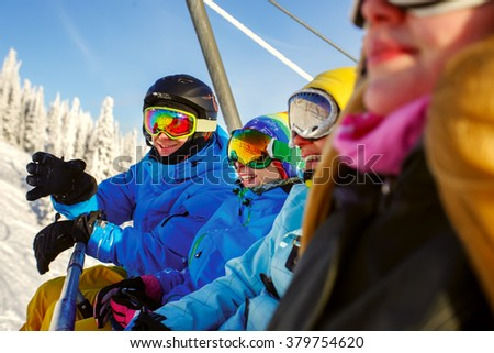 A group of young snowboarders on a lift - stock photo