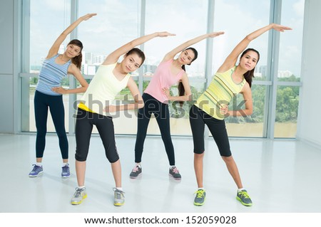 A group of young women warming-up in the aerobics class together - stock photo