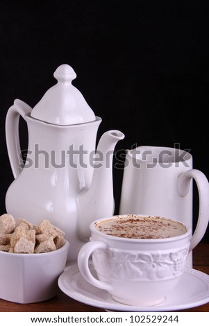 A grouping comprising of a coffee pot, sugar bowl containing brown sugar cubes, cup of coffee and milk jug.