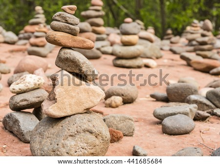 A grouping of small cairns at Buddha Beach near Oak Creek on the Red Rocks Crossing hike in Sedona, AZ. - stock photo