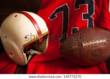 A grouping of vintage, antique american football items including an helmet, jersey, and old leather football - stock photo