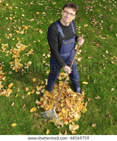 A grown man wearing blue overalls and right in the garden leaves into a heap together, looks into the camera - stock photo