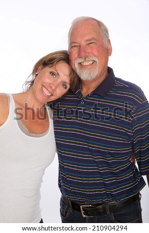 A grown woman rests her head on her mature fathers shoulder - stock photo