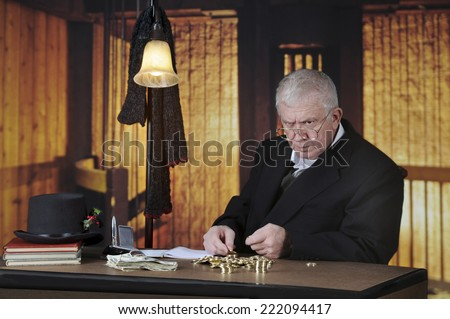A grumpy old miser sitting at his desk counting gold coins by a stack of big bills.