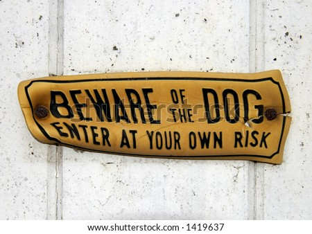 A grungy, distorted, 'Beware of the Dog' sign, nailed to a wooden gate. Clipping path, around the sign, included so it can be extracted and placed on any other background. - stock photo