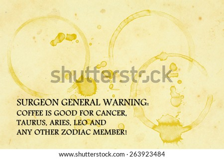 "A grungy paper napkin with coffee mug stains and a funny quote ""Surgeon General Warning: Coffee is good for Cancer, Taurus, Aries, Leo and other zodiac member!"". - stock photo"