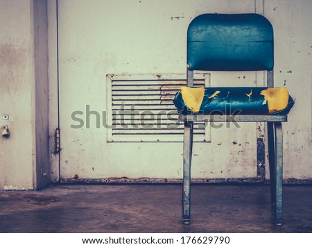A Grungy Retro Damaged Chair Outside  A Workplace - stock photo