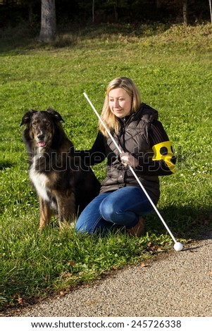 A guide dog sitting next to a blind woman on a meadow - stock photo