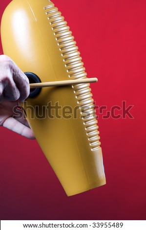 A guiro gourd percussion instrument being played against a red background in the vertical format with copy space. - stock photo