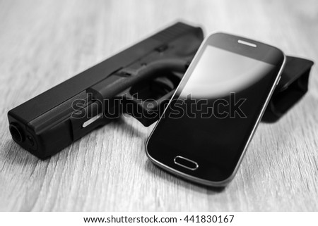 A gun and a modern smart phone, black and white