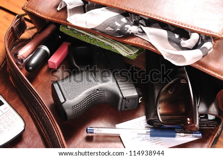 a gun in a purse - stock photo