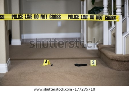 a gun lying on the ground next to a crime scene marker. - stock photo