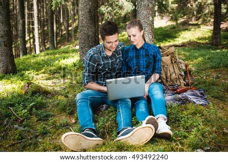 A guy and a girl tourists relax in the mountain forest, sitting and looking at laptop
