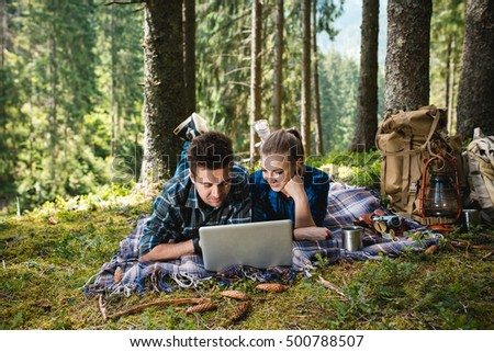 A guy and a girl tourists rest in the forest and looking in laptop