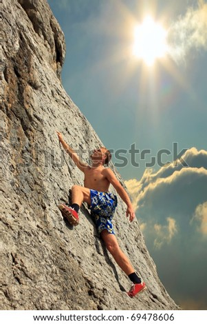 A guy climbs on a rock against the sky with a sunset - stock photo
