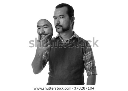A Guy holding a own mask in black and white photography. Hypocritical, insincere, two-faced emotion face. - stock photo