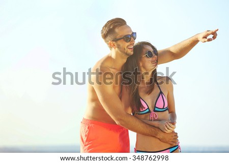 A guy hugging a girl at the beach, on sky background
