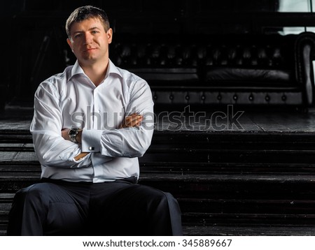A guy in a white shirt on wooden stairs