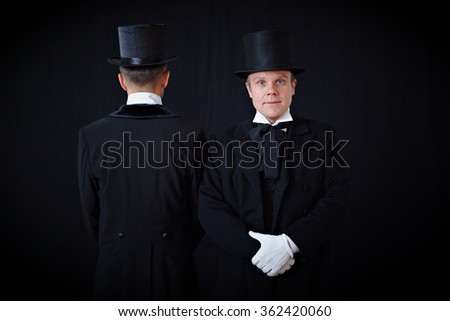 a guy in an old black tuxedo and hat