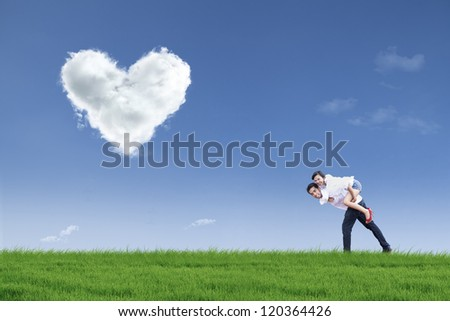 A guy is giving his girlfriend a piggyback ride in green field during Valentine's day