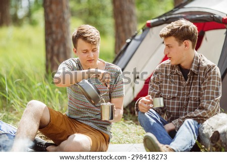 A guy making himself tea while talking to his friend in the forest