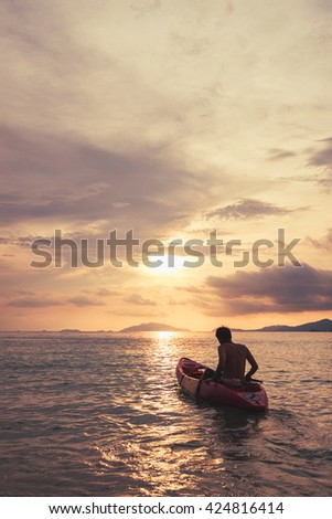 a guy on kayak boating to sunset, vintage tone, abstract concept  - stock photo