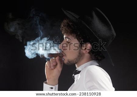a guy smoking a cigar havana on a dark background - stock photo