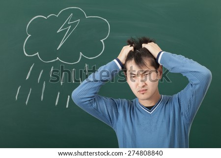 A guy with a bad mood, drawn on a blackboard cloud and rain - stock photo