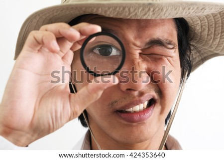a guy with explorer hat look through magnifying glass