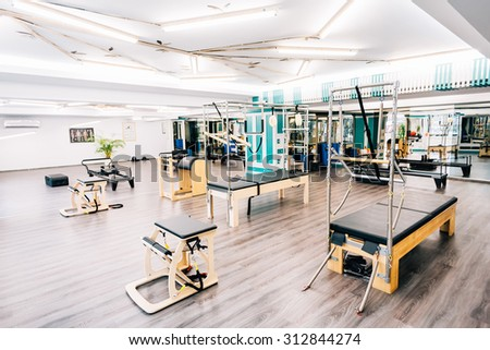 A gym full of pilates equipment: exochairs, ladder barrel, reformer, cadillac, trapeze table and other. - stock photo