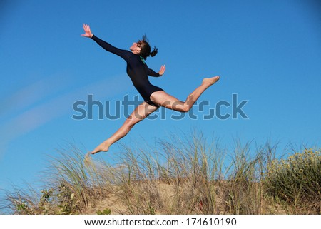 A gymnast is doing her routine on the beach in South Africa. - stock photo