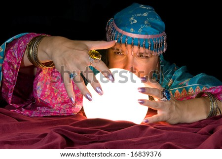 A gypsy fortune teller brings her crystal ball to life to read the future. - stock photo