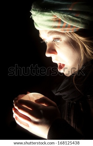 a gypsy looking at her crystal ball with a shocked expression. - stock photo